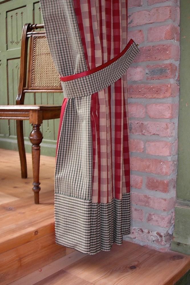 Gardine im Landhausstil mit Raffband in klassischen roten und grünen Karos.