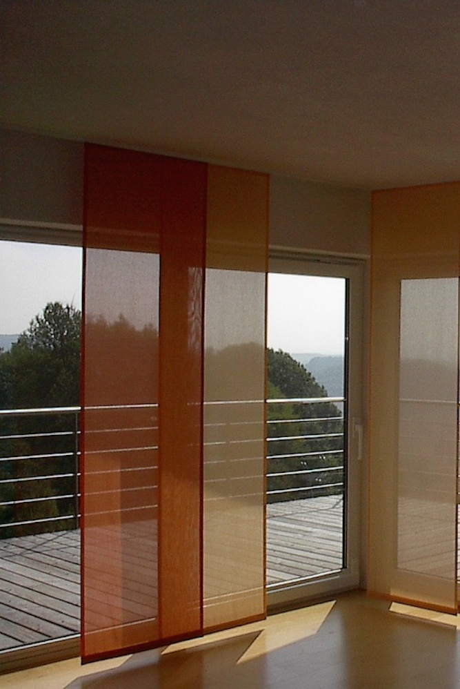 Die Schiebegardienen in warmen Farben bieten einen Blick- und Sonnenschutz und lassen den Raum trotzdem hell erscheinen.