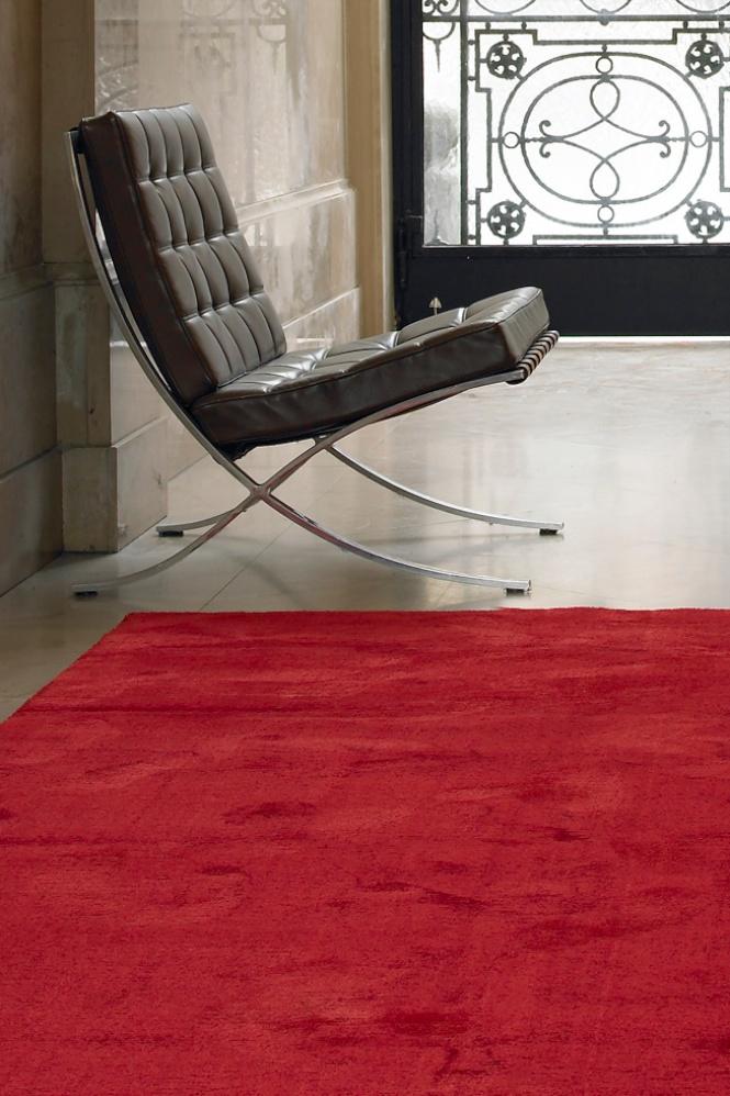 Ein ganz flacher Teppich aus rotem Velour.
