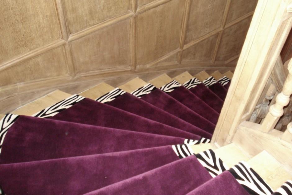 Im Saarland kommen Sie am Besten zu Rainer Scheid - textiler Wohnen, wenn Sie einen Teppich für Ihre Treppe suchen. Unsere Treppenteppiche werden extra für Sie gefertigt, wie dieser hochwertige Teppich aus lilafarbener Wolle mit Zebra-Randmuster.