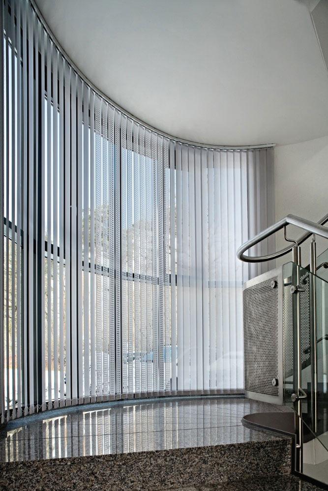 Die Schienen von vertikalen Jalousien lassen sich an Rundungen anpassen. Somit folgt der Sichtschutz den Formen des Raumes.
