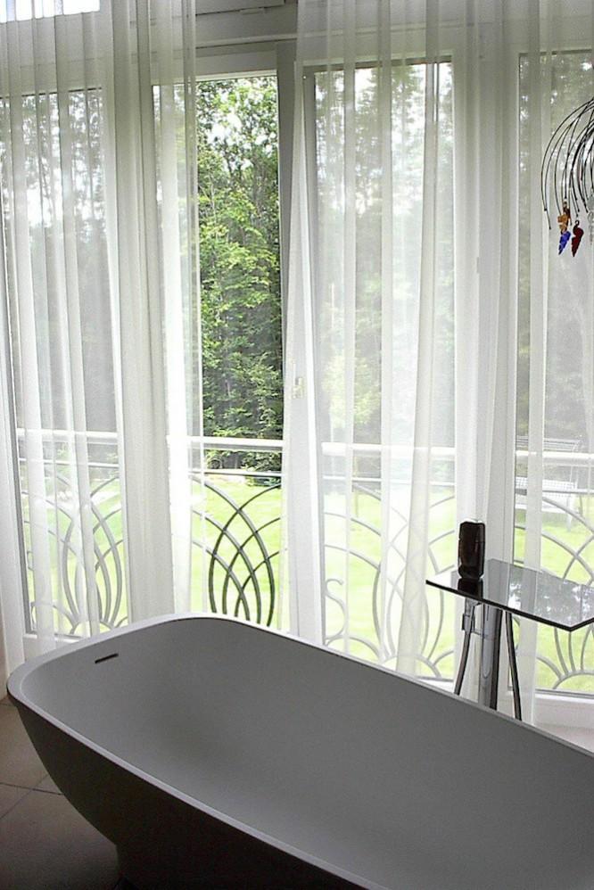 Die transparente Gardine im Bad unterstreicht den eleganten Wohnraumcharakter.