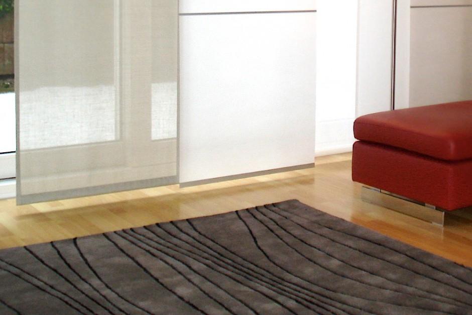 """Flacher, wohnlicher Teppich mit einem Linienrelief in der Farbe """"Taupe"""" passt sehr gut zu den roten Möbeln."""