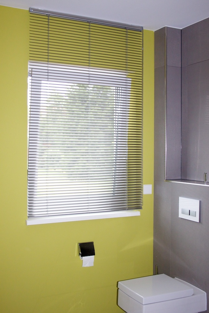 Vertikaljalousien sind ideal für intime Räume wie Bäder oder WCs. Durch die verstellbaren Lamellen dringt Licht in den Raum ohne dass jemand hineinsehen kann. Privatsphäre garantiert.